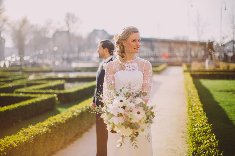 Wedding day photo of bride and groom in a manicured Amsterdam garden. Photograph captured by Eliska at Khiria Photography